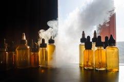 Concetto di Vape Nuvole di fumo e bottiglie liquide del vape sulla finestra con luce solare su fondo Effetti della luce Utile com Immagine Stock Libera da Diritti