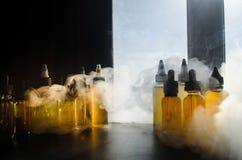 Concetto di Vape Nuvole di fumo e bottiglie liquide del vape sulla finestra con luce solare su fondo Effetti della luce Utile com Immagini Stock