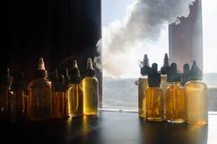 Concetto di Vape Nuvole di fumo e bottiglie liquide del vape sulla finestra con luce solare su fondo Effetti della luce Utile com Immagine Stock