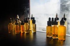 Concetto di Vape Nuvole di fumo e bottiglie liquide del vape sulla finestra con luce solare su fondo Effetti della luce Utile com Fotografia Stock