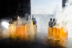 Concetto di Vape Nuvole di fumo e bottiglie liquide del vape sulla finestra con luce solare su fondo Effetti della luce Utile com Fotografia Stock Libera da Diritti