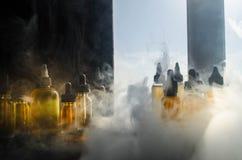 Concetto di Vape Nuvole di fumo e bottiglie liquide del vape sulla finestra con luce solare su fondo Effetti della luce Utile com Fotografie Stock Libere da Diritti
