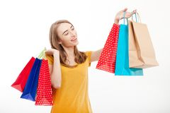 Concetto di vendita del negozio di estate Bella giovane donna con i sacchetti della spesa e lo stile casuale Jeans e camicia gial Immagine Stock