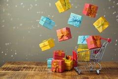 Concetto di vendita di festa di Natale con i contenitori di regalo e di carrello Immagine Stock