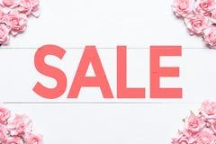 Concetto di vendita - mano con la lente d'ingrandimento Blocco per grafici dentellare delle rose Immagini Stock
