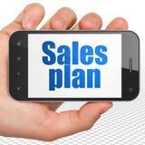 Concetto di vendita: Passi la tenuta dello Smartphone con il piano di vendite su esposizione Fotografia Stock