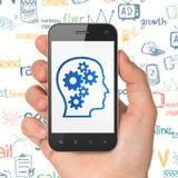 Concetto di vendita: Passi la tenuta dello Smartphone con la testa con gli ingranaggi su esposizione Fotografia Stock