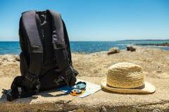 Concetto di viaggio con il cappello dello zaino, della mappa, della bussola e di paglia Fotografia Stock