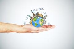 Concetto di viaggio con la mano dell'uomo e la terra rotonda con i punti di riferimento Immagini Stock Libere da Diritti