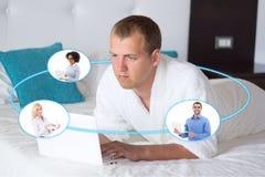 Concetto di viaggio di affari - giovane uomo di affari con il computer portatile in hotel Immagini Stock Libere da Diritti