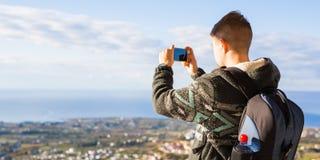 Concetto di viaggio, di vacanza, del fotografo e dell'autostoppista - l'uomo del raveler ha fotografato le montagne e la città ne Fotografia Stock Libera da Diritti