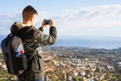 Concetto di viaggio, di vacanza, del fotografo e dell'autostoppista - l'uomo del raveler ha fotografato le montagne e la città ne Fotografie Stock