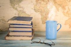 Concetto di viaggio e di studio Pila di vecchi libri e di tazza di Dott. caldo Fotografie Stock