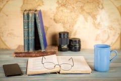 Concetto di viaggio e di studio Vecchi libri, una tazza della bevanda calda, smartph Fotografie Stock Libere da Diritti