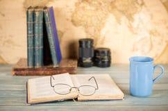 Concetto di viaggio e di studio Vecchi libri, una tazza della bevanda calda, vetri Immagine Stock