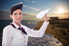 Concetto di viaggio - hostess con l'aereo di carta sopra la spiaggia b di tramonto immagine stock libera da diritti