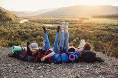 Concetto di viaggio, di turismo e di amicizia Gruppo di giovani amici che viaggiano insieme in montagne Pantaloni a vita bassa fe fotografia stock libera da diritti