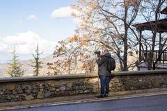 Concetto di viaggio, di vacanza, del fotografo e dell'autostoppista - l'uomo del viaggiatore ha fotografato la città Immagini Stock Libere da Diritti