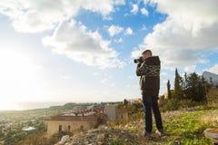 Concetto di viaggio, di vacanza, del fotografo e dell'autostoppista - l'uomo del viaggiatore ha fotografato la natura Fotografia Stock