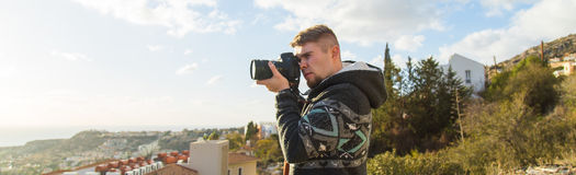 Concetto di viaggio, di vacanza, del fotografo e dell'autostoppista - l'uomo del viaggiatore ha fotografato le montagne e la citt Immagine Stock Libera da Diritti