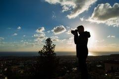 Concetto di viaggio, di vacanza, del fotografo e dell'autostoppista - la siluetta dell'uomo del viaggiatore ha fotografato la nat Fotografia Stock Libera da Diritti