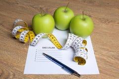 Concetto di Weightloss - vicino su di carta con il piano di dieta, mele immagine stock