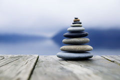 Concetto di Zen Balancing Pebbles Misty Lake immagine stock