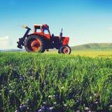 Concetto a distanza tranquillo del campo del sobborgo di agricoltura del trattore Immagini Stock Libere da Diritti