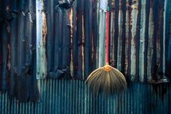 Concetto domestico delle attrezzature per la pulizia sulla parete antica dello zinco Immagini Stock Libere da Diritti