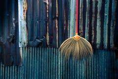 Concetto domestico delle attrezzature per la pulizia sulla parete antica dello zinco fotografia stock