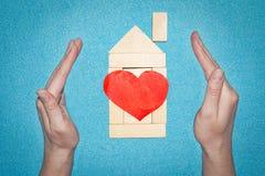 Concetto domestico di assicurazione Camera dai mattoni di legno dentro le mani Camera con cuore rosso Amore nel concetto domestic Fotografia Stock Libera da Diritti