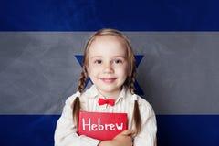 Concetto ebraico con lo studente della bambina contro la bandiera di Israele immagini stock
