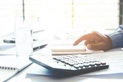 Concetto economico di costo calcolatore di contabilità dell'uomo di affari fotografia stock