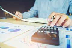 Concetto economico di costo calcolatore di contabilità dell'uomo di affari fotografie stock