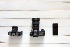 Concetto evolventesi di tecnologie Macchina da presa d'annata, macchina fotografica digitale, Smartphone su fondo di legno bianco Immagine Stock