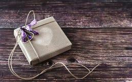Concetto fatto a mano del regalo La carta del mestiere ricicla il contenitore di regalo con i fiori sulla tavola di legno Vista s fotografia stock libera da diritti