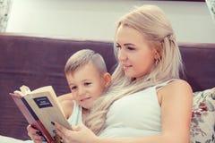 Concetto felice di infanzia Mamma e figlio che leggono un libro nel letto r fotografie stock libere da diritti