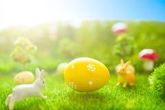 Concetto felice di Pasqua Coniglietto di pasqua ed uova di Pasqua su erba verde Tramonto di fiaba sul campo verde di plastica con Immagine Stock
