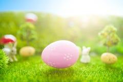 Concetto felice di Pasqua Coniglietto di pasqua ed uova di Pasqua su erba verde Tramonto di fiaba sul campo verde di plastica con Fotografia Stock