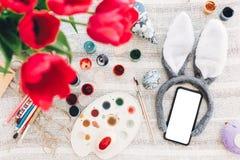 Concetto felice di Pasqua orecchie e telefono del coniglietto con lo schermo vuoto e immagine stock