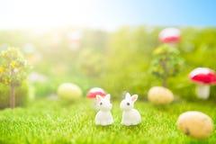 Concetto felice di Pasqua Pochi giocattoli del coniglietto di pasqua ed uova di Pasqua su erba verde Tramonto di fiaba sul campo  Immagine Stock Libera da Diritti