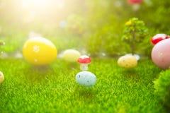 Concetto felice di Pasqua Uova di Pasqua Su erba verde Tramonto di fiaba sul campo verde di plastica con erba, i funghi e la t di Fotografia Stock