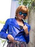 Concetto femminile di bellezza Ritratto della ragazza alla moda nella posa di lusso blu del rivestimento e degli occhiali da sole Immagini Stock Libere da Diritti