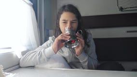 Concetto ferroviario di viaggio bambina al tè delle bevande della finestra in un vagone del compartimento tè caldo delle bevande  archivi video