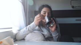 Concetto ferroviario di viaggio bambina allo stile di vita del tè delle bevande della finestra in un vagone del compartimento bev stock footage