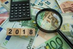 Concetto finanziario di imposta come lente d'ingrandimento sul mucchio di euro bankno Fotografie Stock
