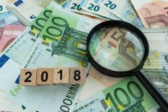 Concetto finanziario di imposta come lente d'ingrandimento sul mucchio di euro bankno Immagini Stock