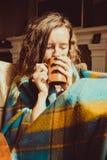 Concetto freddo di malattia di inverno Giovane donna di congelamento del ritratto in sedia comoda con la tazza di tè avvolta in c Immagine Stock