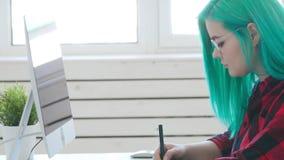 Concetto freelancing o del lavoro d'ufficio Giovane grafico femminile con capelli colorati che funzionano nell'ufficio o a casa stock footage