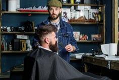 Concetto governare Barbiere occupato con la barba governare del cliente dei pantaloni a vita bassa, rifornimenti di bellezza su f fotografie stock